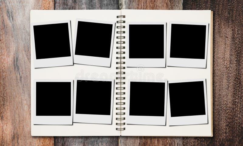 Strutture in bianco della foto nell'album di foto, sugli ambiti di provenienza di legno dello scrittorio fotografie stock libere da diritti