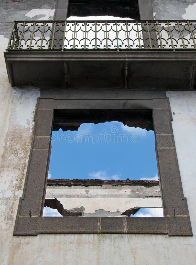 Strutture della finestra vuote in una casa abbandonata senza tetto con un balcone e pareti interne bianche contro un cielo blu fotografia stock