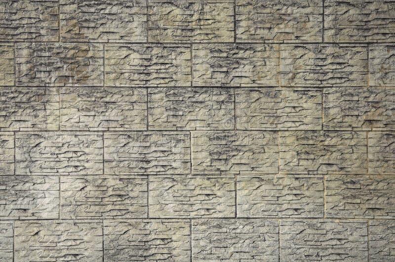 Strutture di pietra del fondo Pietra decorativa grigia sporca del fronte del mattone immagine stock