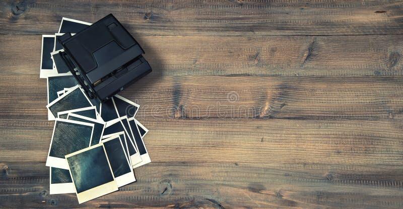 Strutture istantanee d'annata e macchina fotografica della foto sul backgro di legno rustico fotografia stock