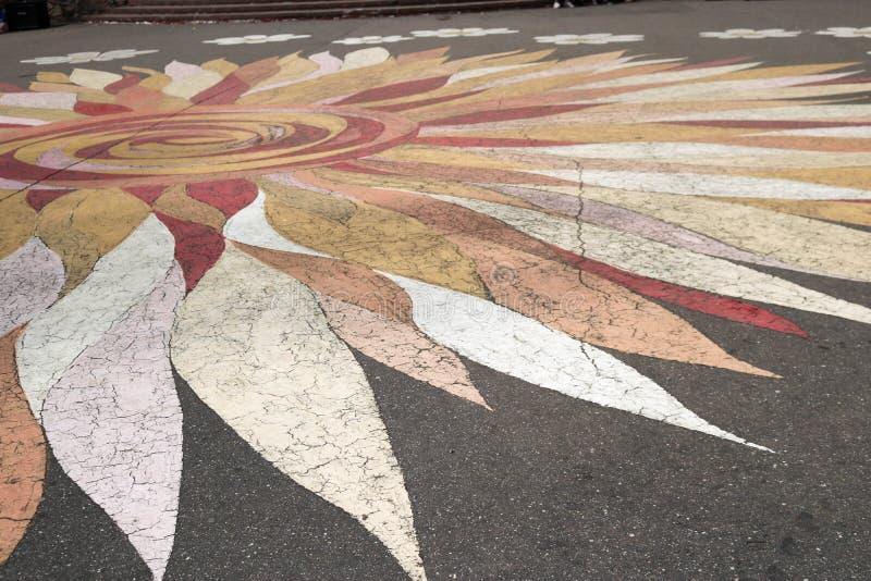 Strutturi il modello sotto forma di un fiore con i petali di bello variopinto sull'asfalto della strada I cenni storici immagine stock