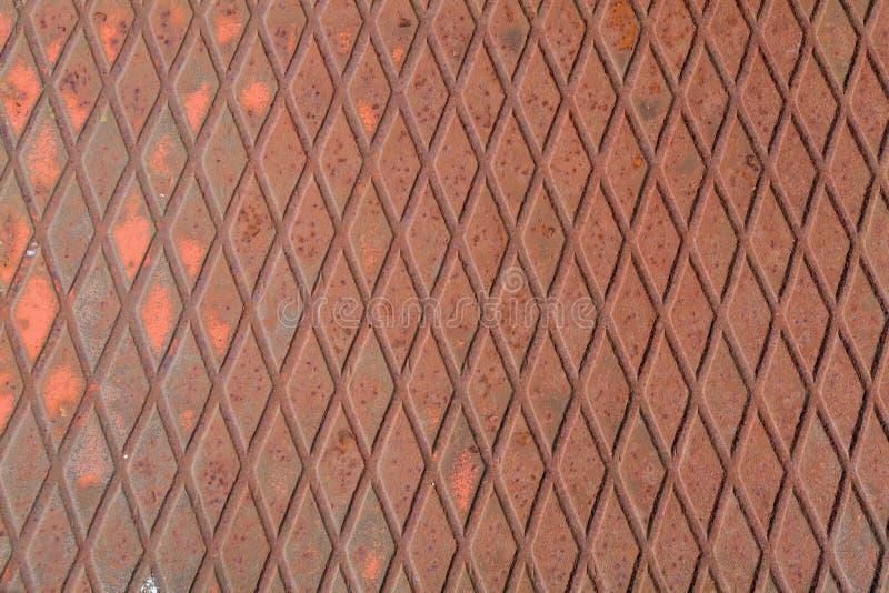 Stryka bakgrund, rostig textur, korrugerad stålplatta med röda fläckar av målarfärg arkivfoto