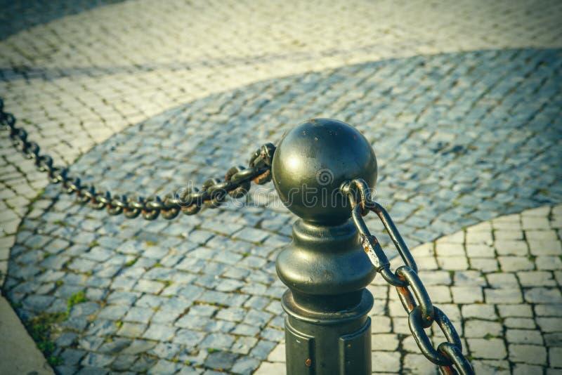 Stryka den gamla pelaren med kedjan på trottoaren nära vägen arkivfoto