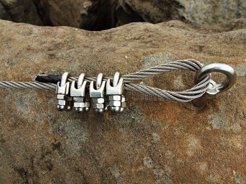 Stryka det vridna repet som fixas i kvarter av skruvsnaphooks. Detalj av slutet av det förankrade repet arkivbild