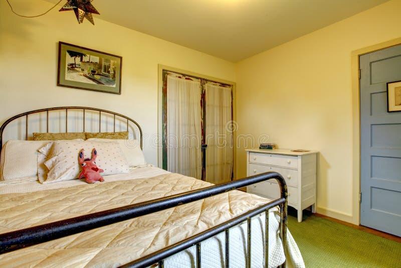 Stryker det hem- sovrummet för landet med sängen och den gammala dörren. arkivbild