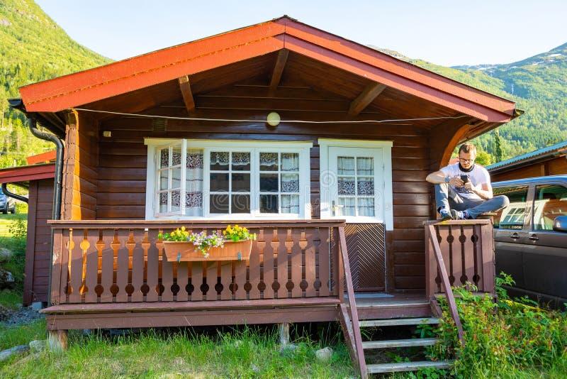 Stryn, Norvegia - 26 06 2018: Uomo in cabine di campeggio rosse per i viaggiatori in Strynsvatn che si accampano, Norvegia fotografia stock libera da diritti