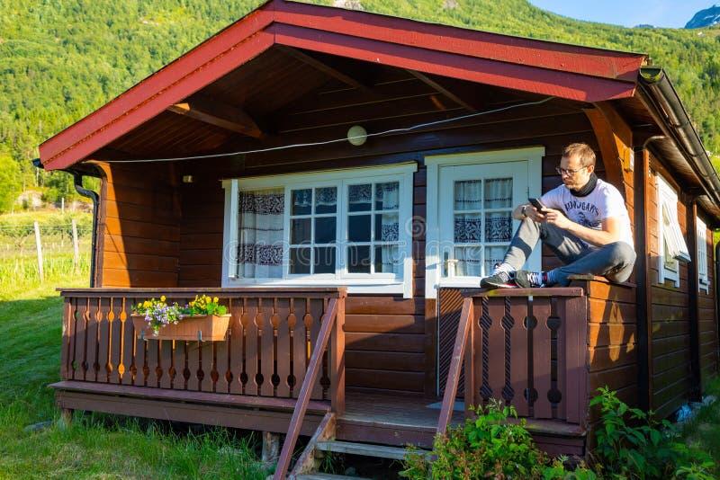 Stryn, Norvegia - 26 06 2018: Uomo in cabine di campeggio rosse per i viaggiatori in Strynsvatn che si accampano, Norvegia immagine stock