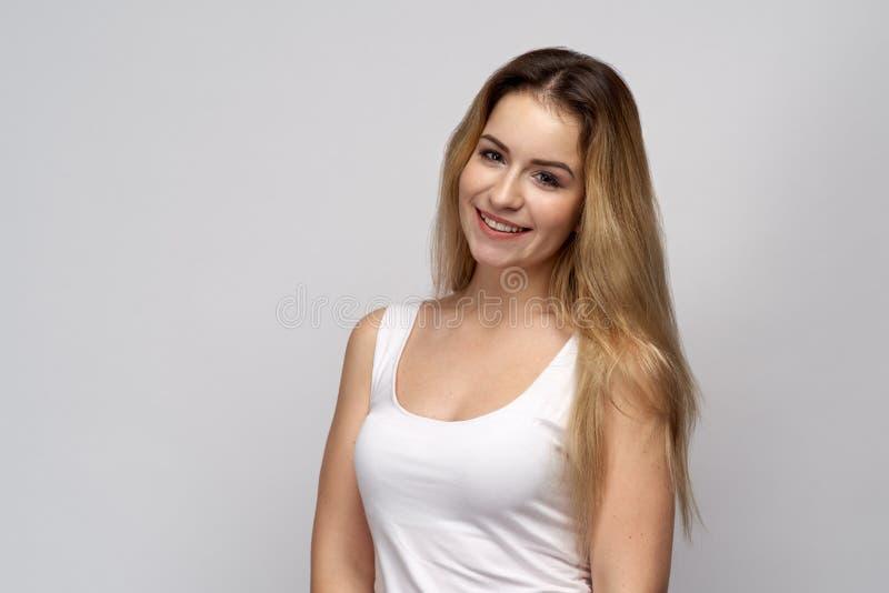 Strzał śliczny kobieta model na odosobnionym białym tle Piękna blondynki dziewczyna jest szczęśliwa otrzymywać komplementy od męż zdjęcie royalty free