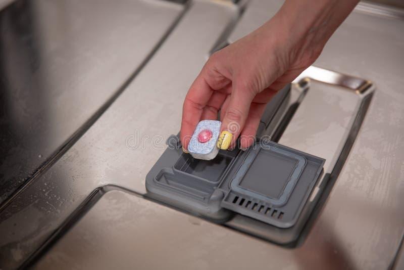 Strzał kobiety ręki kładzenia mydła teblet w zmywarkiego do naczyń pudełku zdjęcia stock