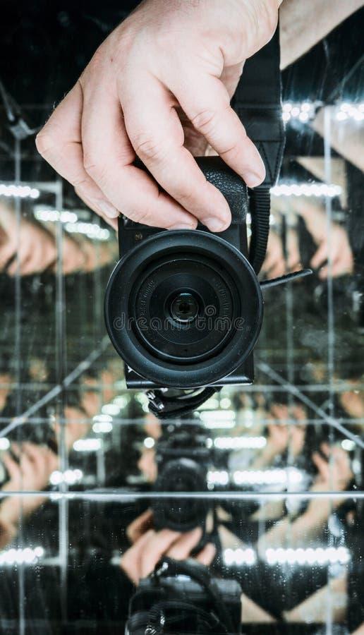 Strzał mężczyzna ręki mienia fotografii kamera w lustrzanym sześcianie zdjęcia royalty free