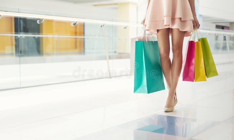 Strzał młoda kobieta iść na piechotę niosący kolorowych torba na zakupy zdjęcie stock