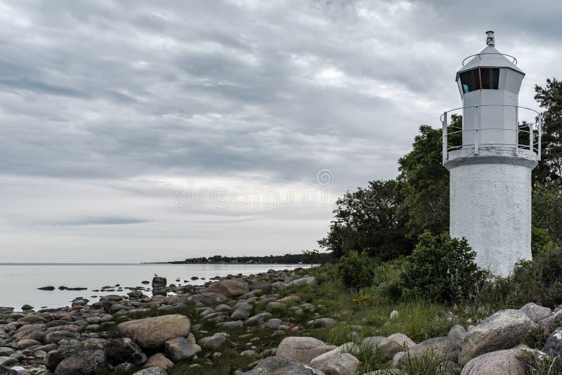 Strzał piękny skalisty wybrzeże morze z biały latarni morskiej wierza na stronie obraz royalty free