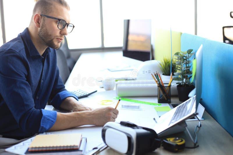 StrzaÅ' przystojnego architekta pracujÄ…cego nad projektem w swoim biurze zdjęcia stock