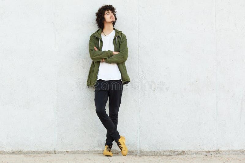 Strzał rozważny marzycielski chłodno facet jest ubranym zielonego eleganckiego anorak, sneakers, utrzymanie ręki składać, podwyżk zdjęcie royalty free