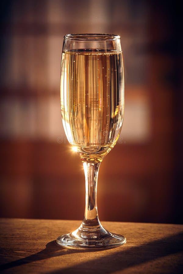 Strzał szampański szkło na drewnianym stole Światło słoneczne i bubb obraz stock