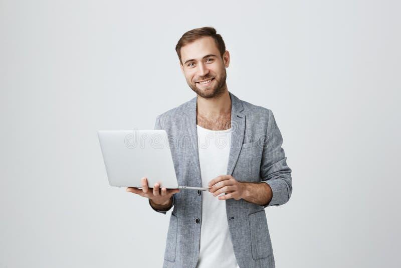 Strzał uśmiechać się caucasian brodatej samiec jest ubranym elegancką szarą kurtkę nad białą koszulką, sprawdza informację na lap fotografia stock