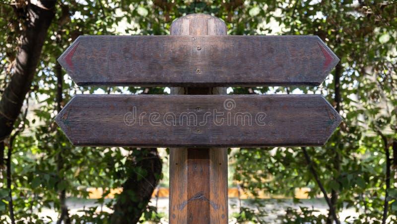Strzałka wskazuje kierunek przeciwny Dwie puste drewniane wskaźniki, tło drzew leśnych, przestrzeń do kopiowania fotografia stock