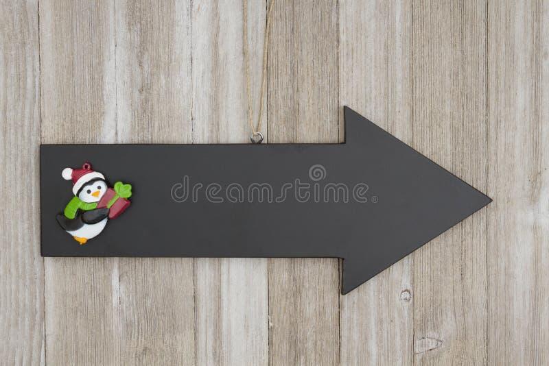 Strzałkowaty chalkboard znak z Bożenarodzeniowym pingwinem na wietrzejącym drewnie obraz stock
