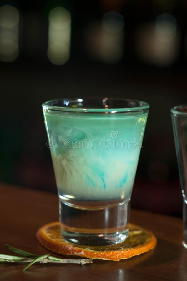 Strzału szkło z błękitnym alkoholu napojem na wysuszonym pomarańczowym plasterku z rozmarynami na drewnianym stole fotografia stock