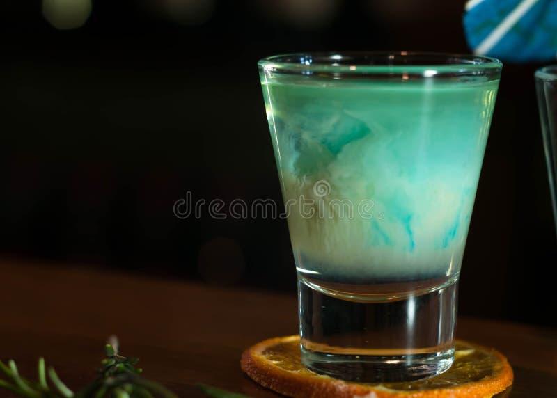 Strzału szkło z błękitnym i białym alkoholu napojem na wysuszonym pomarańczowym plasterku z rozmarynami na drewnianym stole obrazy royalty free
