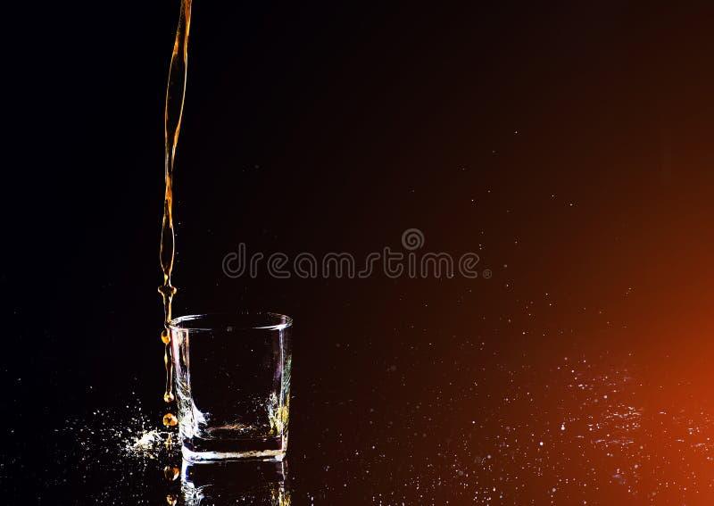 strza? whisky z plu?ni?ciem na czarnym tle, brandy w szkle obraz royalty free