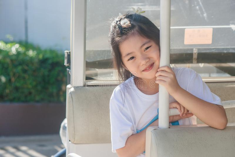 Strzela Azjatyckiej małej ślicznej dziewczyny jest usytuowanym w goft ono uśmiecha się i samochodzie obrazy stock