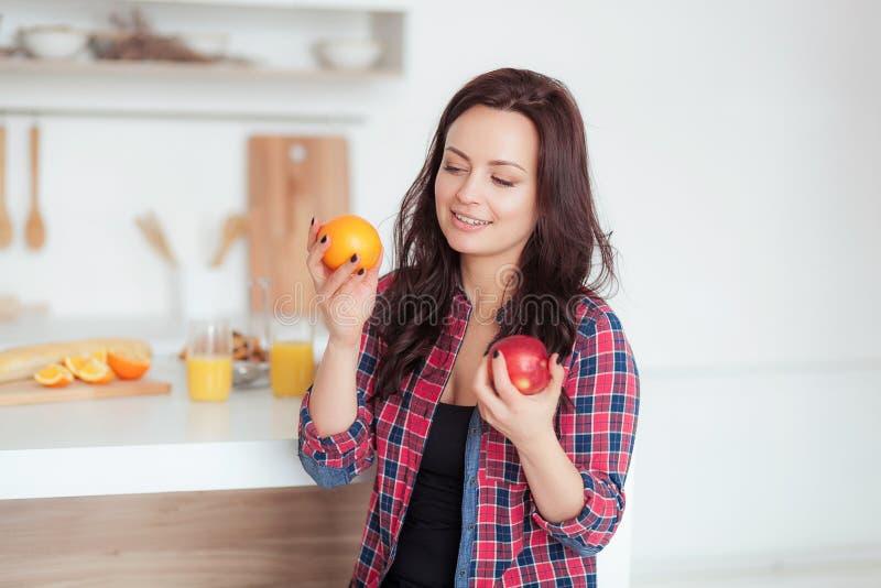 Strzelający ciemna z włosami caucasian kobieta porównuje jabłka pomarańcze fotografia royalty free