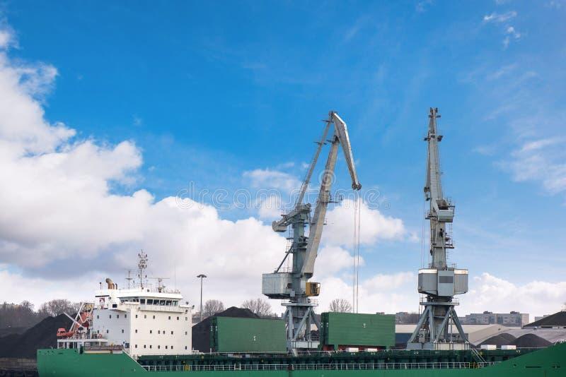 Strzelający dwa stary, ośniedziali, popielaci portowi żurawie z dużymi haczykami, podnośny ładunek w statku na jasnym niebieskieg zdjęcie royalty free