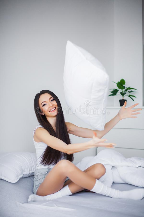 Strzelający młodej kobiety obsiadanie na łóżku obraz royalty free