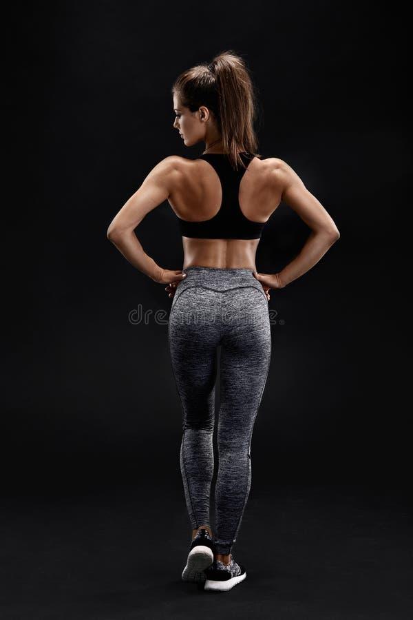 Strzelający silna kobieta z mięśniowym podbrzuszem w sportswear Sprawności fizycznej kobiety wzorcowy pozować na czarnym tle obraz royalty free