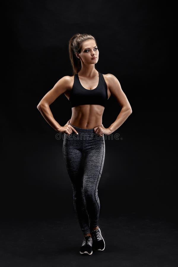 Strzelający silna kobieta z mięśniowym podbrzuszem w sportswear Sprawności fizycznej kobiety wzorcowy pozować na czarnym tle zdjęcia stock