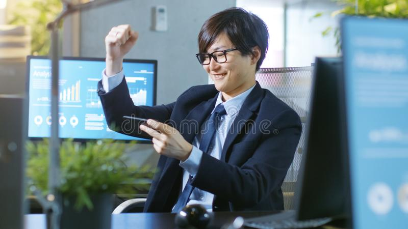 Strzelający Szczęśliwy Wschodnio-azjatycki biznesmena wygranie w Mobilnej grą zdjęcia royalty free