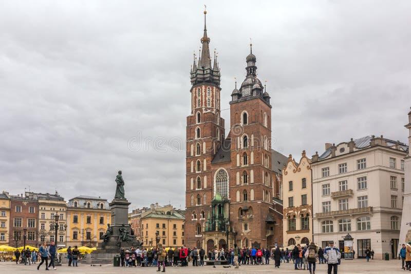 Sts Mary gotiska kyrka på den huvudsakliga marknadsfyrkanten i Krakow på den molniga dagen royaltyfri fotografi
