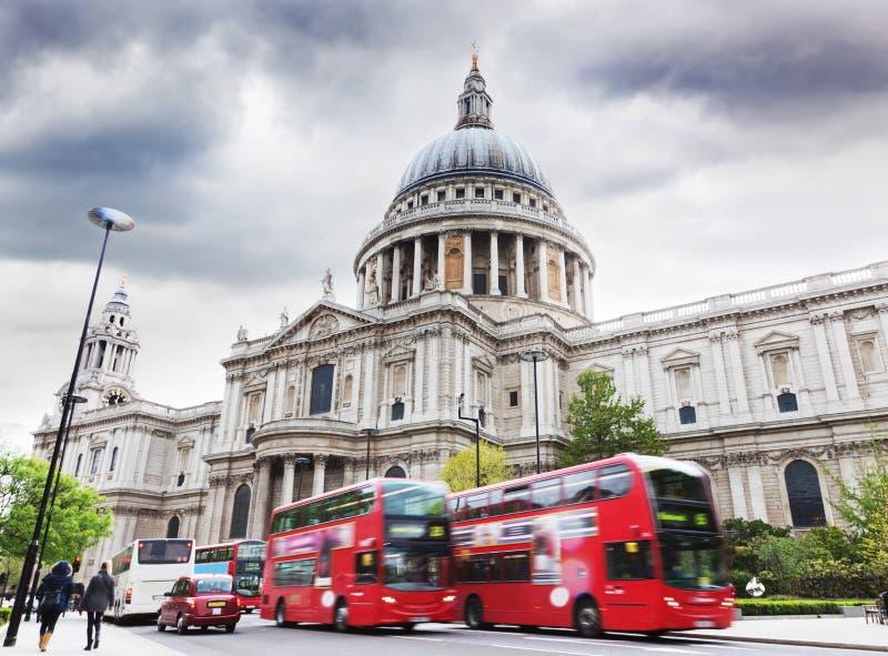 Sts Paul domkyrka i London, UK. Röda bussar arkivbilder
