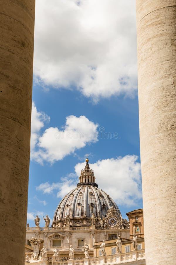 Sts Peter kupol som igenom ses den Bernini kolonnaden i Sts Peter fyrkant, Vatican City arkivfoton