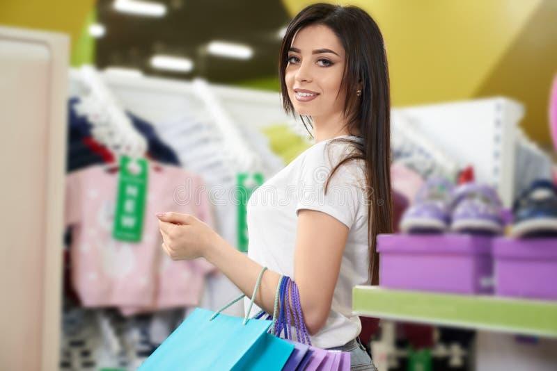 Sttractive brunett som poserar, medan shoppa i lager arkivbild