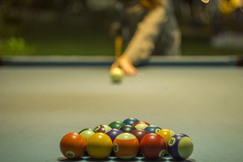 Stubarwne bilardowe piłki kłamają w formie trójgraniastego ostrosłupa na błękitnym płótnie stół przeciw tłu a obraz stock