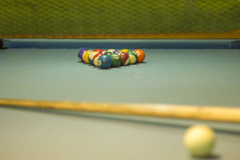 Stubarwne bilardowe piłki z liczbami kłamają w formie ostrosłupa na stole z błękitnym płótnem przeciw tłu a obrazy stock