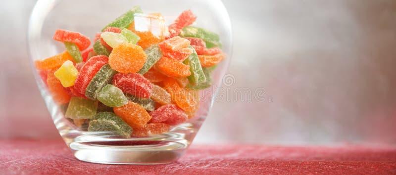 Stubarwne candied owoc w szklanym słoju na srebra tle i czerwieni Miejsce podpisywa? zdjęcia stock