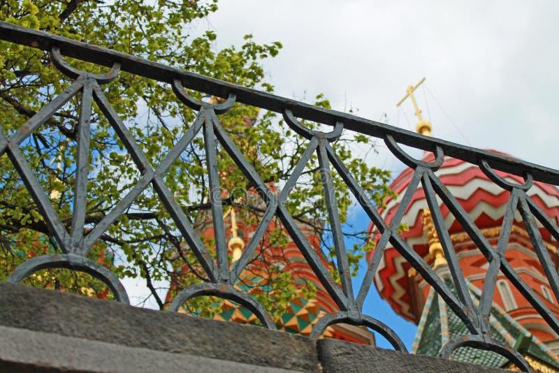 Stubarwne kopuły St basila katedra w Moskwa Rosja przez kratownicy czarny ogrodzenie fotografia stock