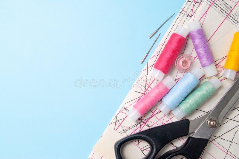 Stubarwne niciane zwitki i pomiarowa taśma na błękitnym tle Szący dostawa nożyce, wzór i akcesoria dla uszycia, obrazy stock