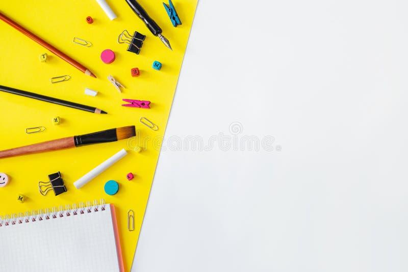 Stubarwne szkolne dostawy na białym i żółtym tle z kopii przestrzenią zdjęcie stock