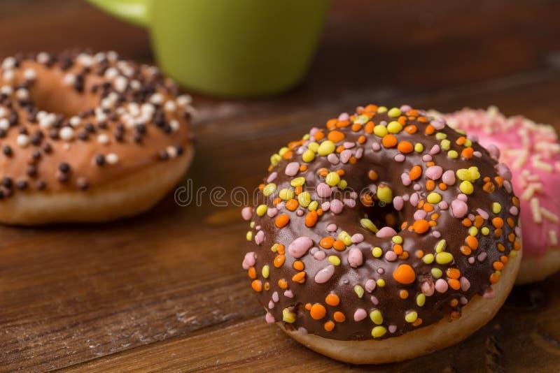 Stubarwni Donuts na drewnianym tle cukierki dla śniadania obraz stock