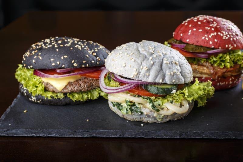 Stubarwni hamburgery na czarnym tle zdjęcia stock