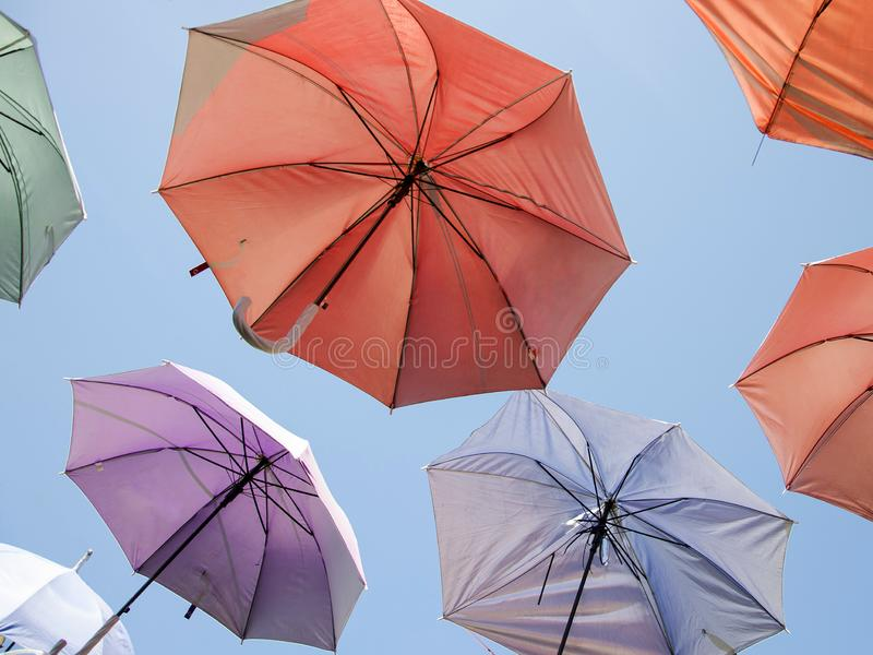 Stubarwni parasole jako uliczna dekoracja na niebieskiego nieba tle fotografia stock