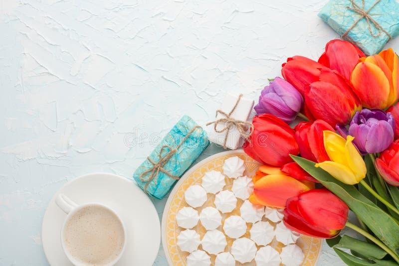 Stubarwni tulipany z kawą, prezenty, bise na lekkim tle i odgórny widok z pustą przestrzenią dla pisać lub reklamować, zdjęcie royalty free