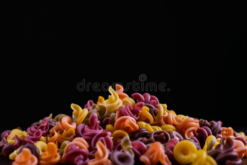 Stubarwny makaron z dodatkiem naturalnego jarzynowego barwidła Kłamają w stosie na czarnym tle zdjęcie royalty free