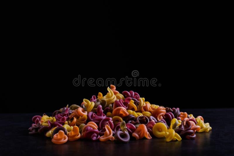 Stubarwny makaron z dodatkiem naturalnego jarzynowego barwidła Kłamają w stosie na czarnym tle fotografia royalty free