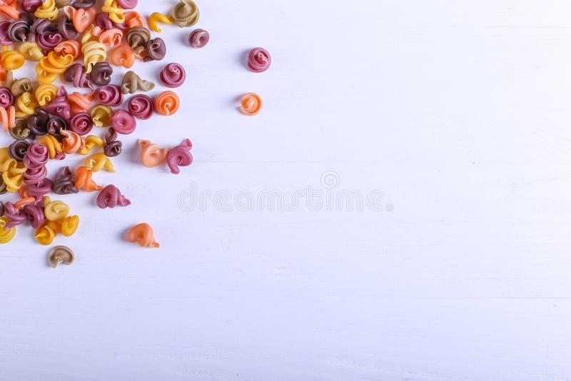 Stubarwny makaron z dodatkiem naturalnego jarzynowego barwidła Rozpraszający na białym stole Odgórny widok, kopii przestrzeń obraz royalty free
