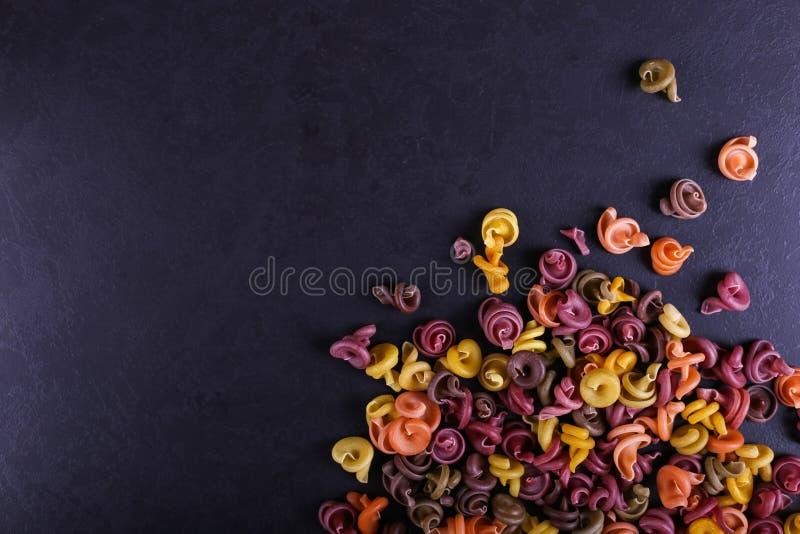 Stubarwny makaron z dodatkiem naturalnego jarzynowego barwidła Rozpraszający na czarnym betonu stole Odgórny widok, kopii przestr obraz royalty free